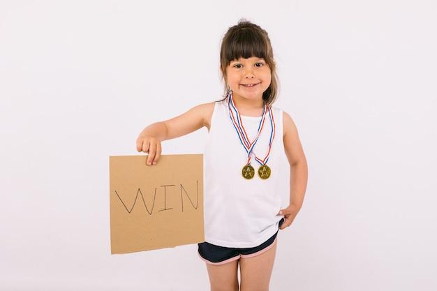 스포츠 챔피언 메달을 가진 작은 검은 머리 소녀, '승리'라는 팻말을 들고 있습니다. 스포츠와 승리 개념