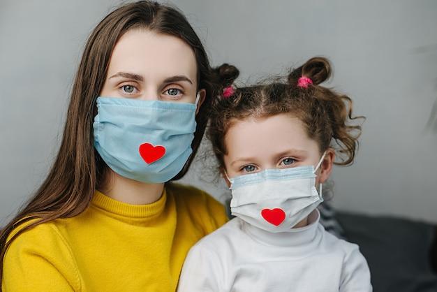 작은 딸과 엄마가 침대에 앉아 포옹하는 것은 카메라를보고 감사를 표시하고 covid-19 전염병 중 모든 필수 직원에게 감사하는 방법으로 붉은 마음으로 마스크를 착용합니다.