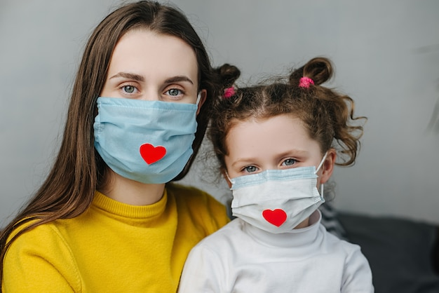 Small daughter and mom hugging her sit on bed look at camera, wearing mask with red heart on it as a way to show appreciation and to thank all essential employees during covid-19 pandemic