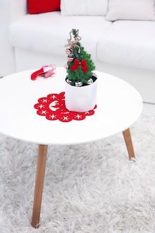 방에 있는 테이블에 작은 장식된 크리스마스 트리를 닫습니다.