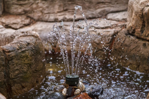 A small decorative fountain among the stones in the city park. short shutter speed