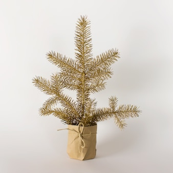 Small decorative golden evergreen fir tree in a pot wrapped with craft paper