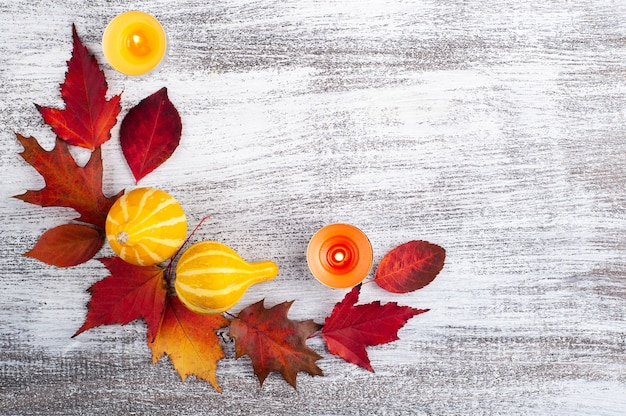 Small decorative pumpkins and falling leaves wreath on rustic wooden table
