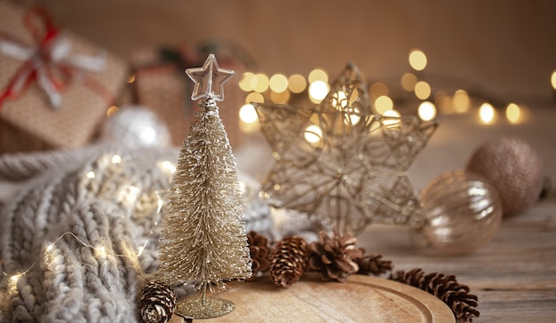 Small decorative shiny christmas tree in close up on a blurred background of christmas decorations, garland and bokeh lights.