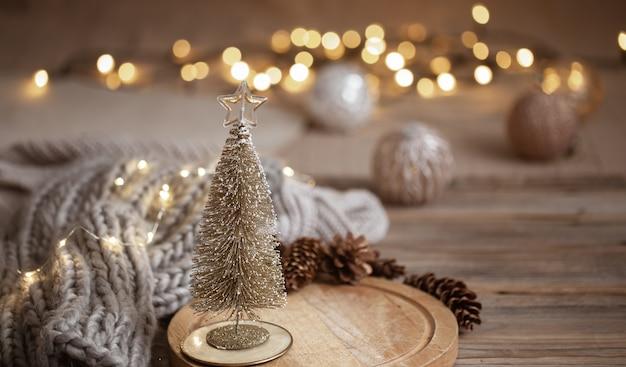 Маленькая декоративная блестящая елка заделывают на фоне размытых огней с боке в теплых тонах.