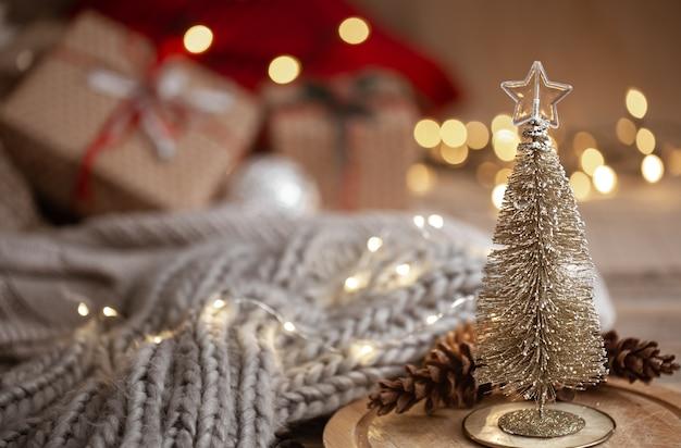 Маленькая декоративная блестящая елка на переднем плане на размытом фоне вязанного шарфа, елочные игрушки и огни боке копируют пространство.