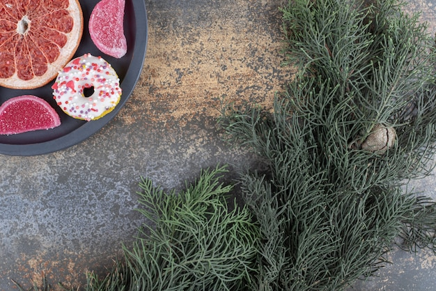 A small donut, marmelades and a grapefruit slice next to a pine branch on wooden surface