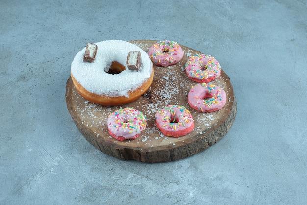 大理石の木の板の上の1つの大きなドーナツの周りの小さなドーナツ。