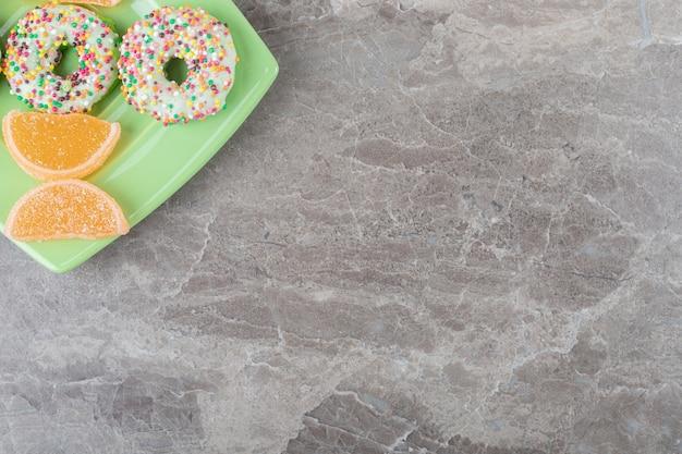 Piccole ciambelle e marmellate disposte su un piatto verde su una superficie di marmo