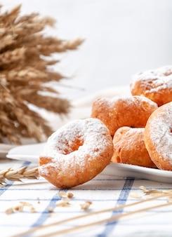 粉砂糖をまぶした小さなドーナツ。白いお皿に。背景には小麦の穂と穀物。