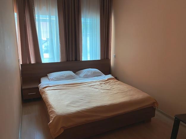 ホテル内の小さなダブルルームで、ベージュ色の小さなエリアとダブルベッドが備わっています。