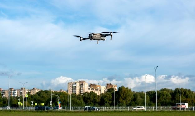 Маленький дрон, летящий в голубом небе над городом