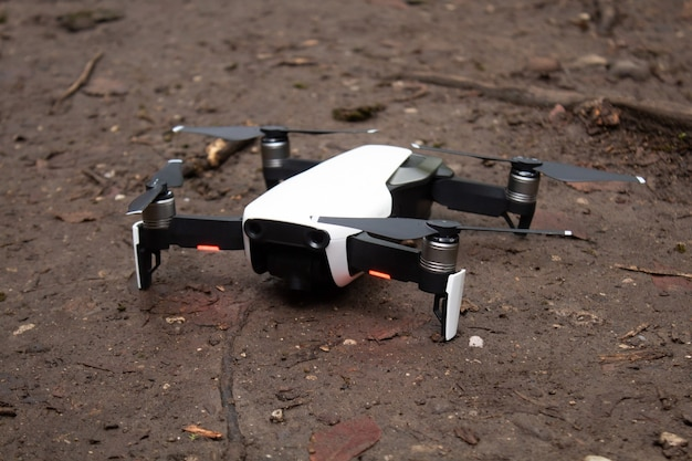 A small drone stands on the ground