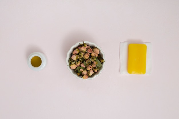 Small dry buds of roses in ceramic white bowl; honey bottle and herbal yellow soap on napkin against textured backdrop