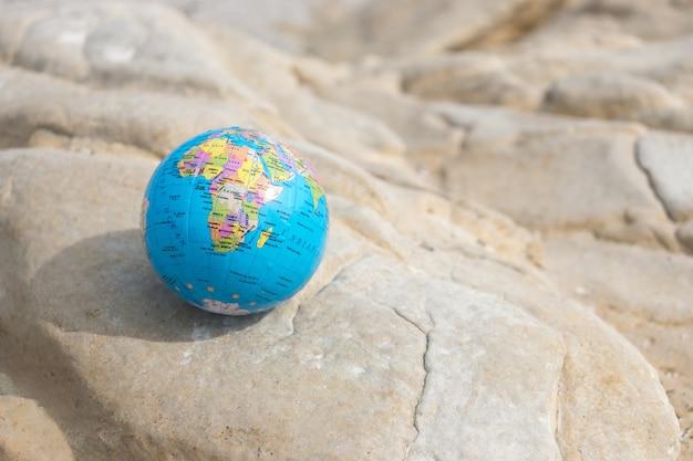 Маленький земной шар лежит на скале концепция путешествий и глобальных проблем