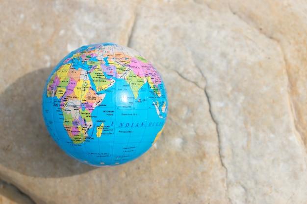Маленький земной шар лежит на скале