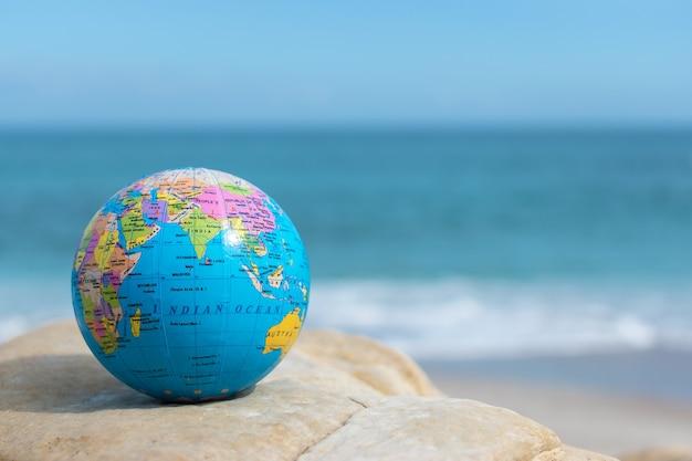 Small earth globe lies on a rock on a tropical beach