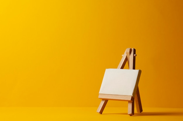 Small empty easel for drawing on a yellow background