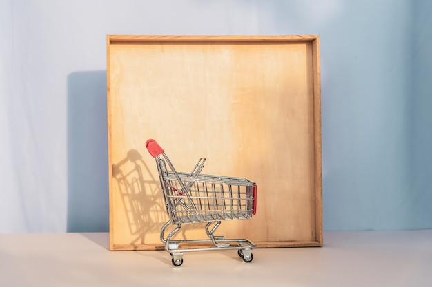 Small empty metal trolley from a supermarket casting a shadow on wooden frame. copy space, template