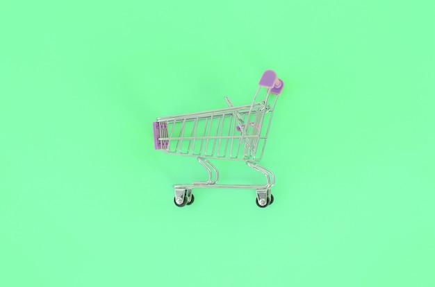 Small empty shopping cart lies on green