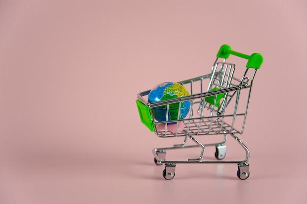 Маленькая пустая тележка для покупок с глобусом на розовом фоне