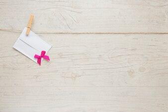 Маленький конверт с бантом, висящий на веревке