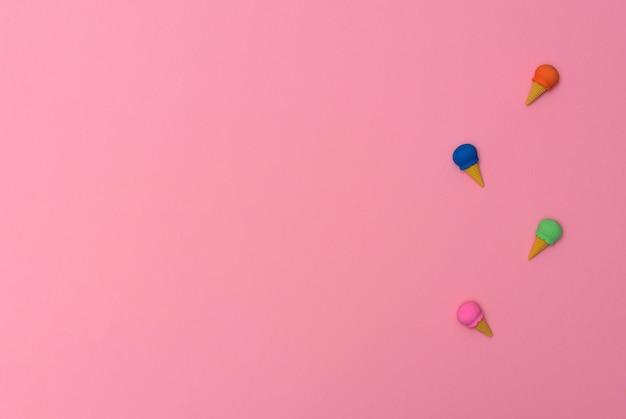 Маленькие ластики в виде мороженого на розовом фоне концепция летнего минимализма плоская планировка