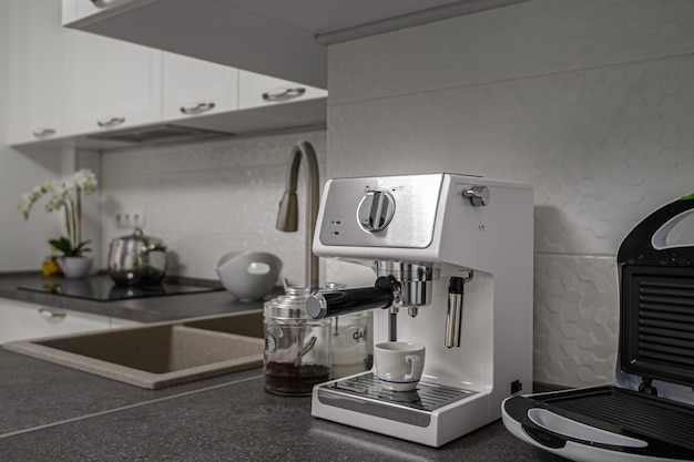 Small espresso coffee maker and roaster in modern minimalistic white kitchen interior