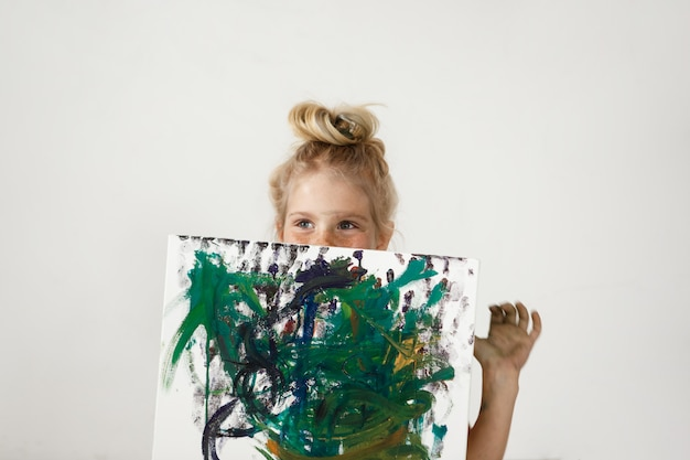 Small european blonde girl with blue eyes and hair bun holding colourful picture and hiding her face. happiness and joy of little girl is so charming. kids` art activities.