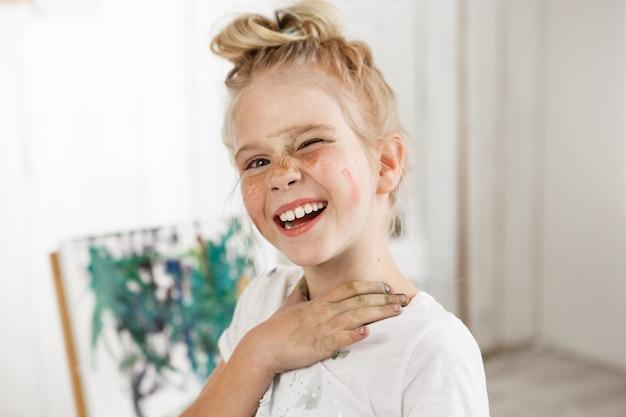 작은 유럽 금발 소녀 그린 얼굴로 웃으면 서 아침 햇살에 곁눈질 흰색 티셔츠를 입은 아이의 시니 룩과 혼합 된 독창적 인 분위기와 밝은 분위기.