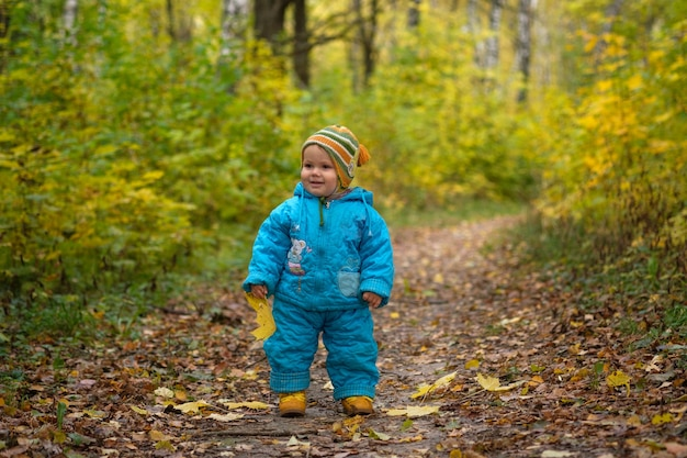 Small european boy with a yellow maple leaf in autumn forest
