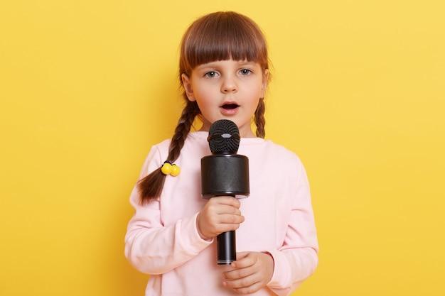 작은 유럽 여자 아이가 마이크에서 노래하고, 집중 해 보이며, 훌륭한 가수가되기를 원하고, 작고 귀여운 아름다운 아티스트가 옅은 분홍색 스웨터를 입고 콘서트를 준비합니다.
