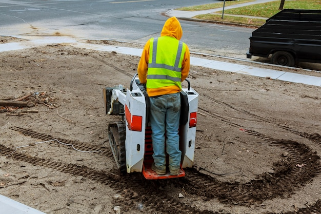 A small excavator works on the street in the summer