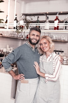 Небольшой семейный бизнес. радостная позитивная пара улыбается вам, владея небольшим кафе