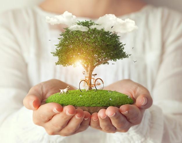 女性の手で木の下に自転車がある小さな幻想的な島