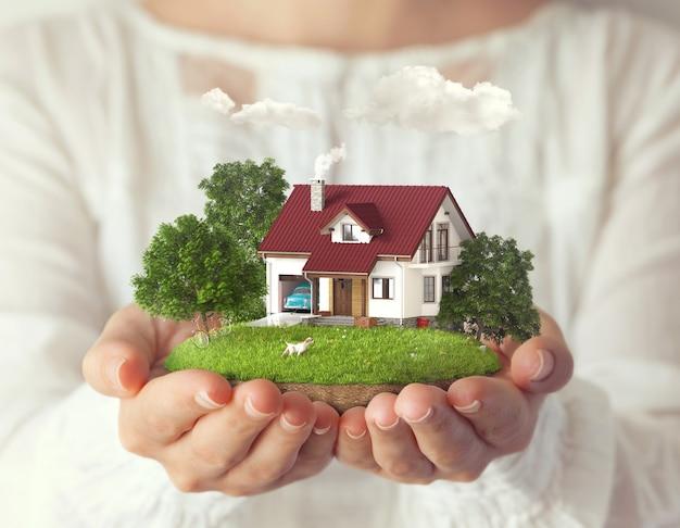 여성의 손에 집과 뒷마당이있는 작은 환상적인 섬