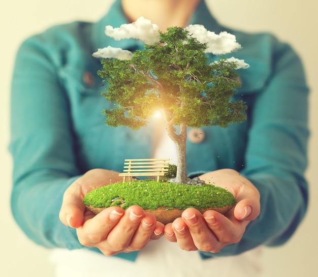 女性の手に木がある小さな幻想的な島