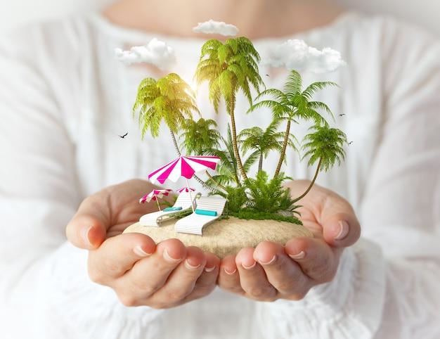 女性の手にサンベッドとヤシの木がある小さな幻想的な島