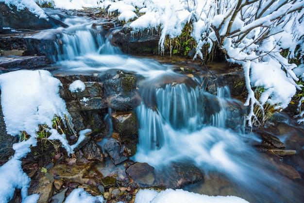 그림 같은대로 산의 작은 젖은 돌과 차가운 하얀 눈 사이의 작은 빠른 흐름