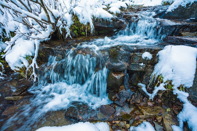 Small fast stream among small wet stones and cold white snow in the picturesque carpathian mountains in beautiful ukraine and its fantastic nature