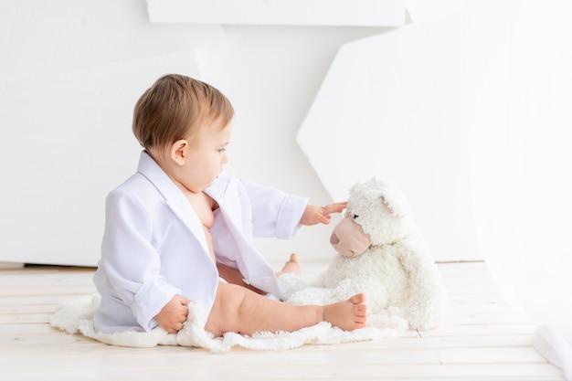 Маленький толстый ребенок в белой куртке и подгузниках играет с мишкой тедди