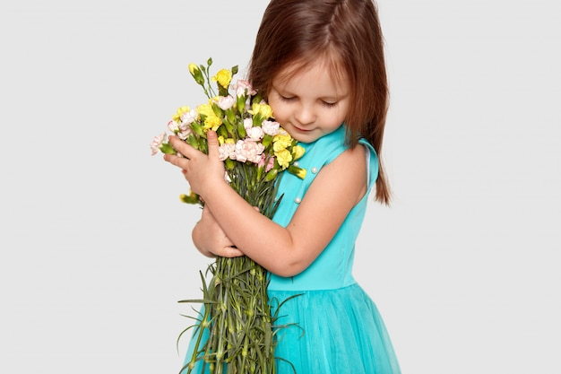 Small female child, focused down, dressed in stylish dress, carries bouquet of spring flowers, poses on white. adorable girl recieves flowers on 8 march.