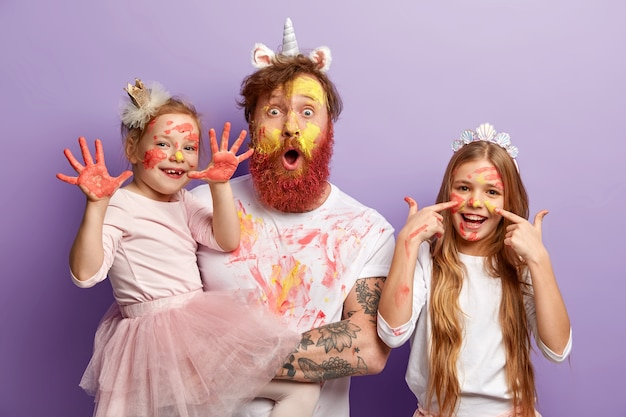 Small female child shows hands soiled with colourful gouache paintings, her glad sister has stains of watercolour on face, stunned father stares, have fun before mother returns from work.