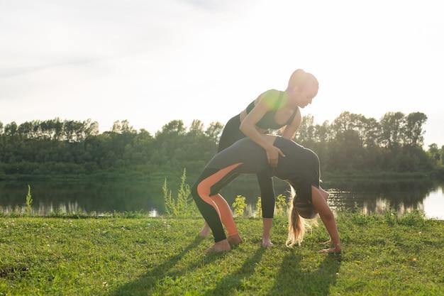 Маленькая женская фитнес-группа занимается йогой в парке в солнечный день