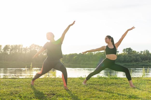 晴れた日に公園でヨガをしている小さな女性のフィットネスグループ
