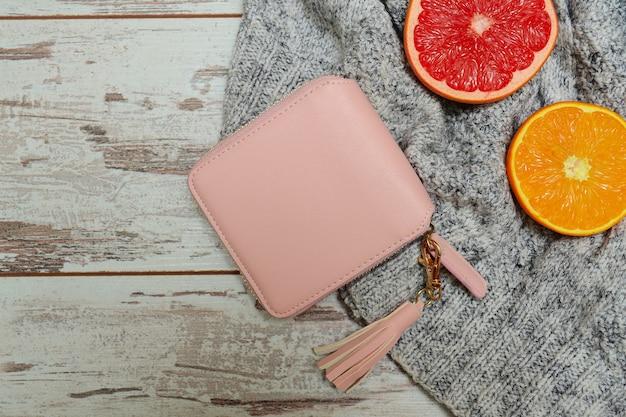 セーターの小さな女性のピンクの財布と柑橘系の果物