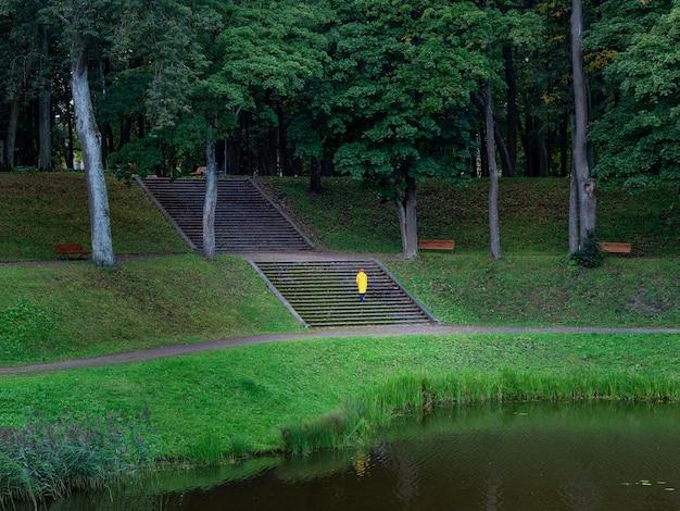 黄色いレインコートを着た女性の小さな姿が石の階段を登る