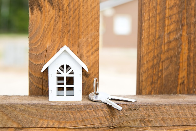 Small figure of white wooden house on fence with key