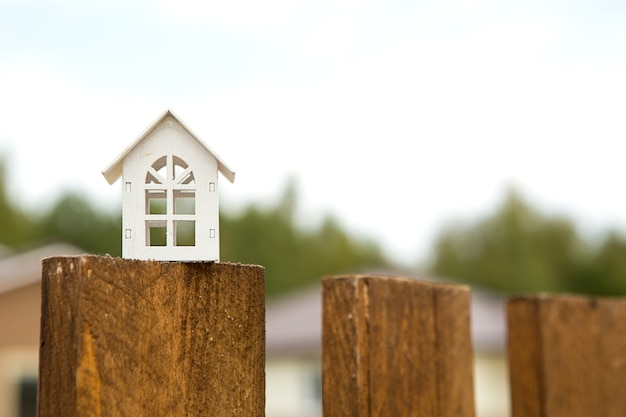 Small figure of white wooden house on fence