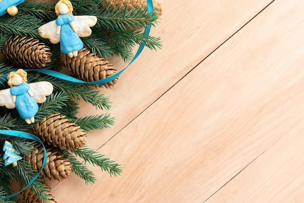 Фигурки ангелов на столе с еловыми ветками.